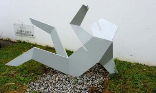 eine liegende Figur aus Stahl, abstrakt
