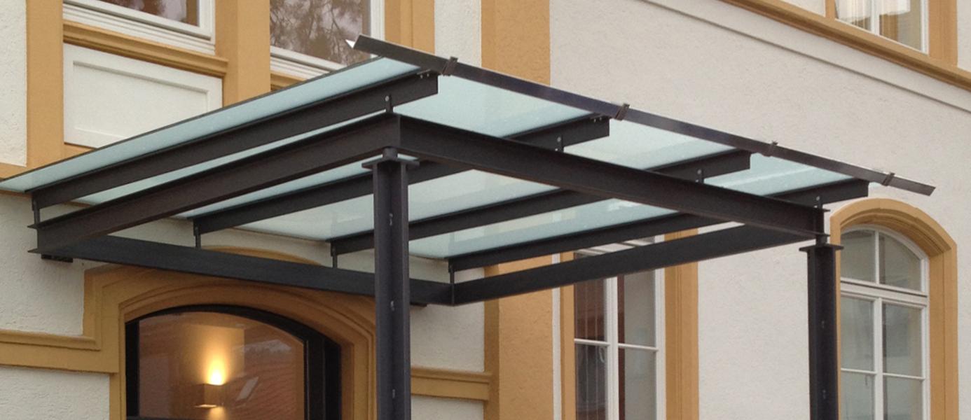 Überdachung des Eingangsbereichs mit Stahlstreben und mattem Glas